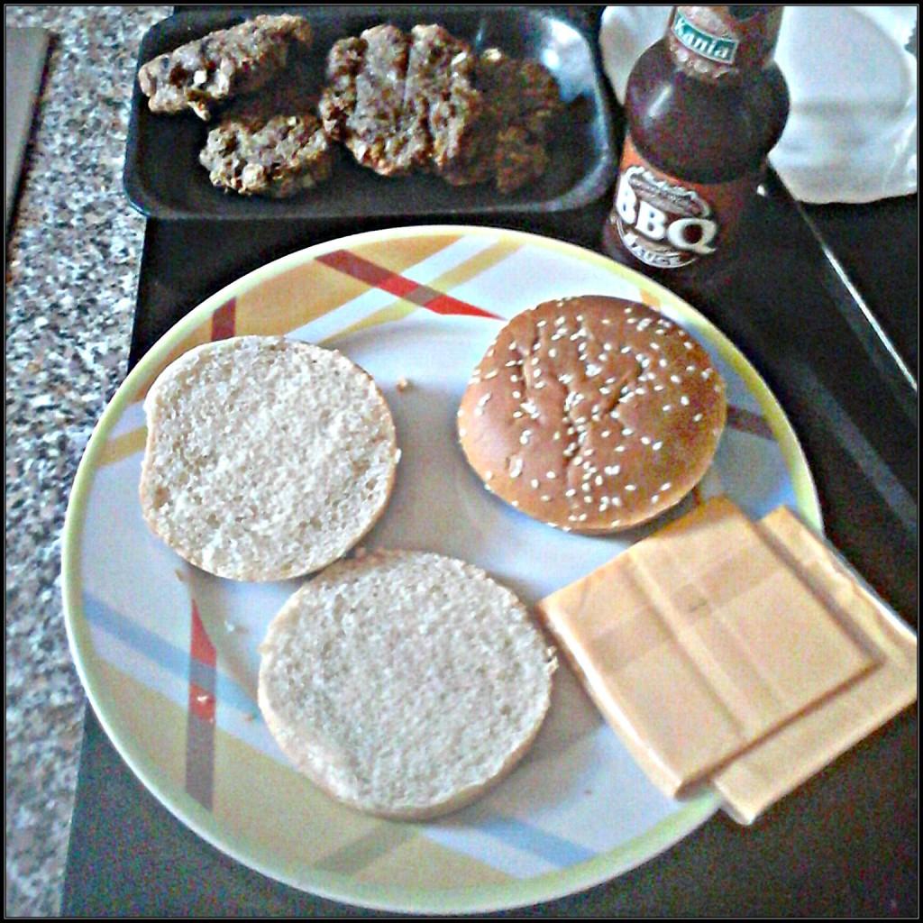 Auf dem Bild, Zwei Burger Brötchen, Patties,, zwei Scheiben Schmelzkäse und Barbecue Soße.